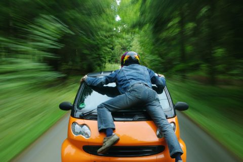 I love this picture of a guy jumping on the front of a smart car.